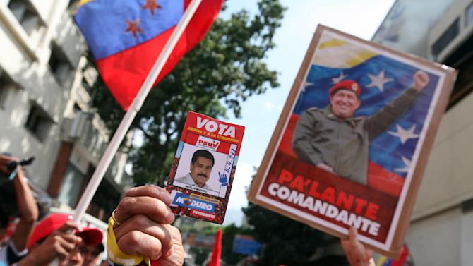 Supporters of President-elect Nicolas Maduro and the late Hugo Chavez gather outside the Parliament building where Maduro's inaugural ceremony takes places, in Caracas, Venezuela, Friday, April 19, 2013. The opposition boycotted the ceremony, hoping that the ruling party's last-minute decision to allow an audit of nearly half the vote could change the result in a the bitterly disputed presidential election.(AP Photo/Gil Montano)
