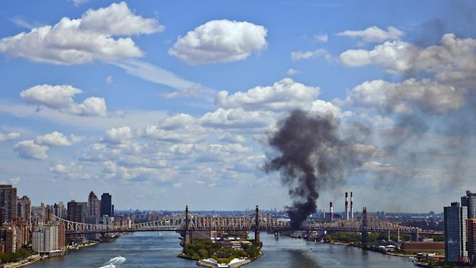 A cloud of smoke billows from the Ed Koch Queensboro Bridge, as seen from Waterside Plaza, on the east side of New York, Friday, Aug. 16, 2013, after a truck caught fire on the bridge. There were no reports of injuries but traffic delays were reported on the major crossing between Manhattan and Queens. (AP Photo/Frank Ritter)