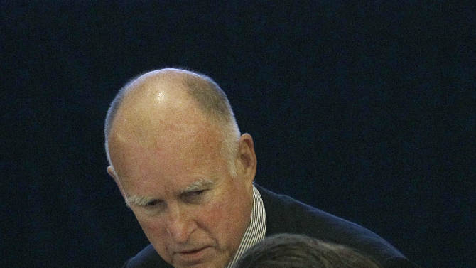 Gov. Jerry Brown, left, talks with Lt. Gov. Gavin Newsom at the UC Board of Regents meeting in San Francisco, Wednesday, Nov. 14, 2012. Brown is set to make his first appearance where he's expected to urge UC officials to control costs and avoid raising tuition. (AP Photo/Jeff Chiu)