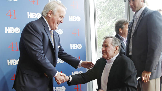 """President George H.W. Bush, right, shakes hands with former Canadian Prime Minister Brian Mulroney as they arrive for the premiere of HBO's new documentary on the president's  life in Kennebunkport, Maine, Tuesday, June 12, 2012.  The premiere of """"41"""" was held Tuesday on Bush's 88th birthday on the grounds of St. Ann's Church in Kennebunkport, near the Bush family's summer home.(AP Photo/Charles Krupa)"""