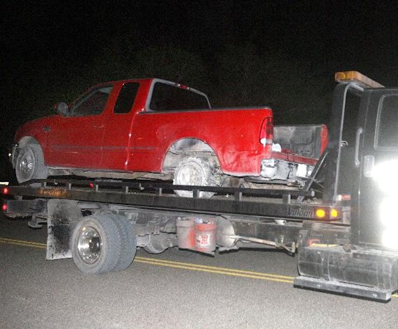 A red pick up truck is moved from the scene of a incident after a chase between law enforcement and suspected human smugglers on 7 mile road north of La Joya, Texas, Thursday, Oct. 25, 2012. Texas Department of Public Safety sharpshooter opened fire on an evading vehicle loaded with suspected illegal immigrants, leaving at least two people dead, sources familiar with the investigation said. (AP Photo/The Monitor, Joel Martinez)