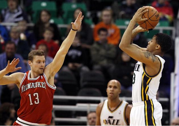 Milwaukee Bucks' Luke Ridnour (13) defends as Utah Jazz's Trey Burke, right, takes a shot in the first half of an NBA basketball game Thursday, Jan. 2, 2014, in Salt Lake City