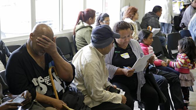 FILE - This March 31, 2014 file photo shows applicants waiting to be called during a health care enrollment event at the Bay Area Rescue Mission in Richmond, Calif. It's not too late to get covered. A few routes remain open for those who missed the health care law's big enrollment deadline. Millions may be eligible for a second chance to sign up for subsidized insurance. And people who get coverage after the deadline can still avoid, or at least reduce, the fine for going uninsured. (AP Photo/Eric Risberg, File)
