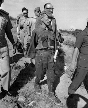 FILE - In this March, 1974 file photo, Hiroo Onoda, wearing his 30-year-old imperial army uniform, cap and sword, walks down a slope as he heads for a helicopter landing site on Lubang Island for a flight to Manila when he comes out of hiding in the jungle on the island, Philippines. Onoda, the last Japanese imperial soldier to emerge from hiding and surrender after World War II, has died. He was 91. Onoda died Thursday, Jan. 16, 2014 at a Tokyo hospital. (AP Photo)