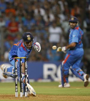 India's captain Mahendra Singh Dhoni, left, escapes a run out during the Cricket World Cup final between India and Sri Lanka in Mumbai, India, Saturday, April 2, 2011. (AP Photo/Kirsty Wigglesworth)