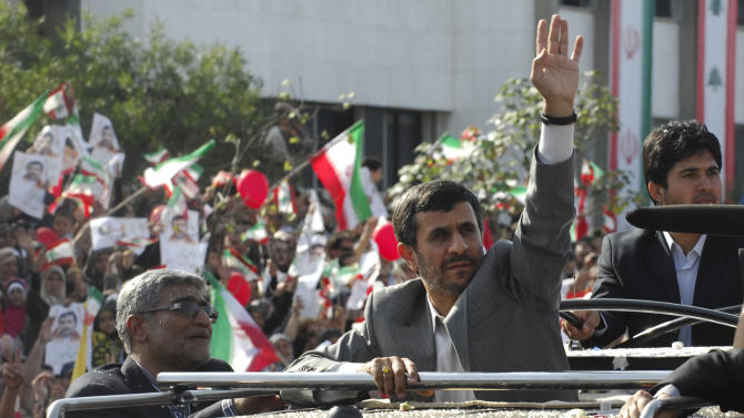 Iranian President Mahmoud Ahmadinejad waves to the crowds from the sunroof of his SUV, upon his arrival in Beirut, Lebanon, Wednesday, Oct. 13, 2010. Thousands of cheering Lebanese welcomed Iranian President Mahmoud Ahmadinejad to Lebanon on Wednesday, throwing rose petals and sweets at his motorcade at the start of a visit that underscores deep divisions within this tiny Arab nation. (AP Photo/Mahmoud Tawil)