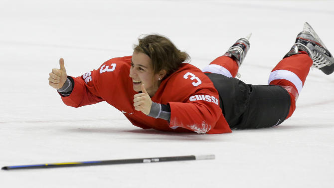 Sarah Forster of Switzerland (3) slides on the ice while celebrating Switzerland's 4-3 win over Sweden in the women's bronze medal ice hockey game at the 2014 Winter Olympics, Thursday, Feb. 20, 2014, in Sochi, Russia. (AP Photo/Matt Slocum)