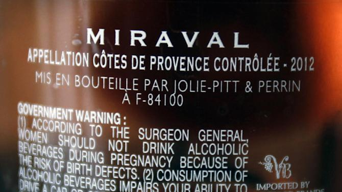 FILE - In this March 7, 2013 file photo, the names of Brad Pitt and Angelina Jolie are visible on a bottle of Miraval, Cote de Provence rose wine displayed in Paris. Jasper Russo, the fine wine buyer for Sigel's wine and spirits store in Dallas, recently held a tasting of celebrity wines, including Miraval, a partnership between Jolie and Pitt and the Perrin French winemaking family.  Miraval retails for about $24.99 and is made from grapes grown at Chateau Miraval, Pitt and Jolie's place in the south of France. (AP Photo/Remy de la Mauviniere, File)