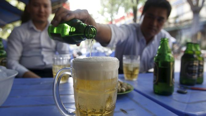 A man pours Saigon beers into a cup at a restaurant in Hanoi, Vietnam