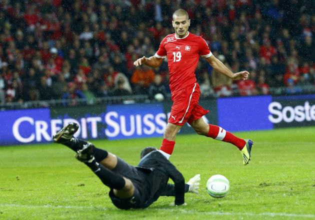 Slovenia's Handanovic makes save in front of Switzerland's Derdiyok during 2014 World Cup qualifying soccer match in Bern