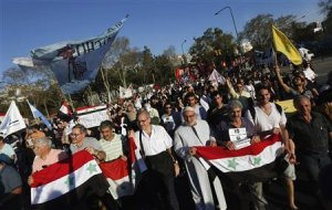 Demonstrators hold up Syrian national flags as they…
