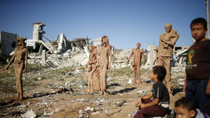 Palestinian boys look at statues in the east of Gaza City