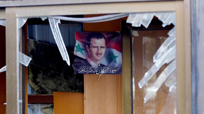 A portrait of Syrian President Bashar Assad is seen through a broken window, hanging on a wall in a building next to the site of a suicide attack at a police officer's club in the Masaken Barzeh district of the capital Damascus