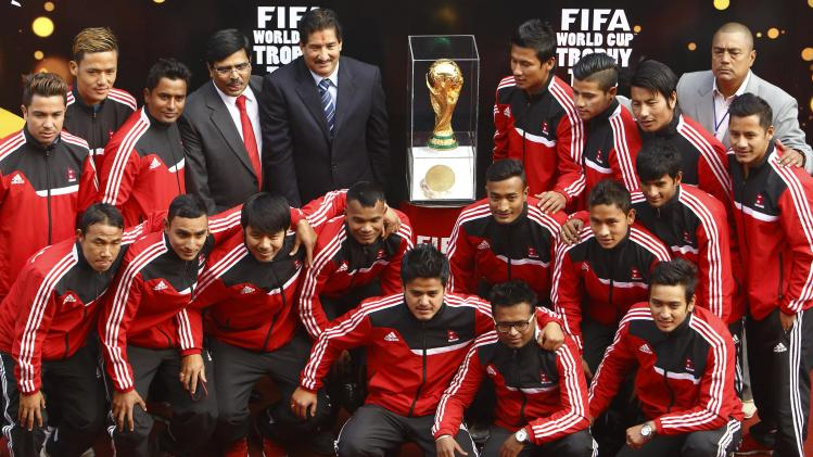 Nepal's national soccer team members pose for a group photo with the World Cup trophy during the FIFA World Cup Trophy Tour in Kathmandu