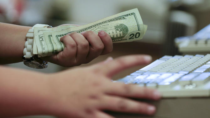 In this Friday, Nov. 23, 2012, photo, a cashier rings up a cash sale at a Sears store, in Las Vegas. U.S. consumers borrowed more in November to buy cars and attend school, but stayed cautious with their credit cards. The Federal Reserve said Tuesday, Jan. 8, 2013, that consumers increased their borrowing in November by $16 billion from October to a seasonally adjusted record of $2.77 trillion. (AP Photo/Julie Jacobson)