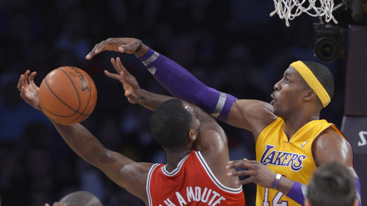 Los Angeles Lakers center Dwight Howard, right, blocks the shot of Milwaukee Bucks forward Luc Richard Mbah a Moute during the first half of an NBA basketball game, Tuesday, Jan. 15, 2013, in Los Angeles. (AP Photo/Mark J. Terrill)