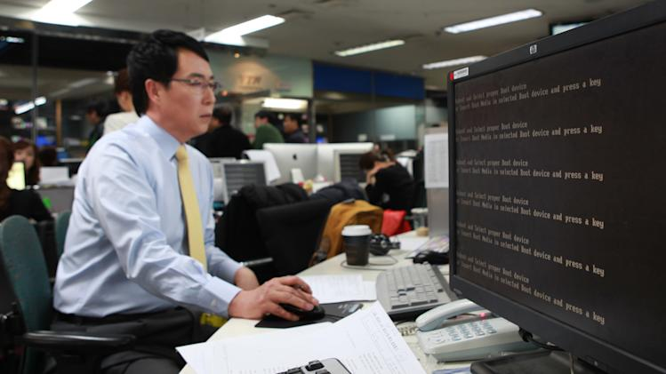 An employee works near a computer screen with error message at the newsroom of the all-news cable channel YTN as the broadcaster's computer network was paralyzed in Seoul, South Korea, Wednesday, March 20, 2013. Computer networks at major South Korean banks and top TV broadcasters crashed en masse Wednesday, paralyzing bank machines across the country and prompting speculation of a cyberattack by North Korea. (AP Photo/Yonhap)  KOREA OUT