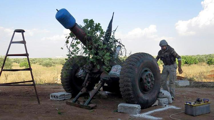 This Tuesday, May 21, 2013 citizen journalism image provided by Edlib News Network, ENN, which has been authenticated based on its contents and other AP reporting, shows a Syrian rebel firing locally made shells made from gas cylinders against the Syrian forces, in Idlib province, northern Syria. Syria's main opposition group is urging rebels to come from around the country to reinforce Qusair, a western town under attack by Syrian troops and members of Lebanon's Hezbollah group. (AP Photo/Edlib News Network ENN)