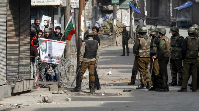 Kashmiri Muslim protesters shout slogans, defying a curfew as India security forces stand in Srinagar, India, Monday, Feb. 11, 2013. Sporadic violence left two people dead in Indian-controlled Kashmir despite a curfew that was extended into a third day Monday in the wake of the execution of a Kashmiri man convicted in a deadly 2001 attack on India's Parliament.(AP Photo/ Mukhtar khan)