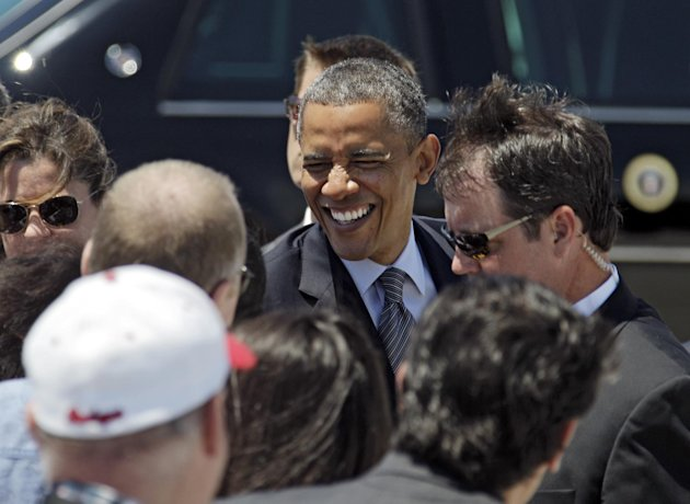President Barack Obama greets supporters after arriving at Cleveland Hopkins International airport in Cleveland, Thursday, June 14, 2012, before attending a campaign event in the city. (AP Photo/Mark Duncan)