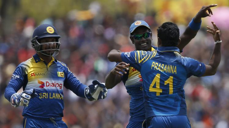 Sri Lanka's Prasanna celebrates with captain Mathews and Sangakkara after taking the wicket of Pakistan's Afridi during their final ODI cricket match in Dambulla