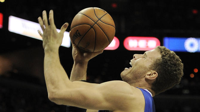 Los Angeles Clippers' Blake Griffin, center, shoots between San Antonio Spurs' Danny Green, left, and Kawhi Leonard during the first half of an NBA basketball game, Friday, March 29, 2013, in San Antonio. (AP Photo/Darren Abate)