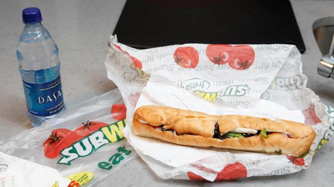"""FILE - This Aug. 11, 2009, file photo, shows a chicken breast sandwich and water from Subway on a kitchen counter in New York. Subway says an ingredient dubbed the """"yoga mat"""" chemical will be entirely phased out of its bread by the week of April 14, 2014. The disclosure comes as Subway has suffered from an onslaught of bad publicity since a food blogger petitioned the chain to remove the ingredient. (AP Photo/Seth Wenig, File)"""