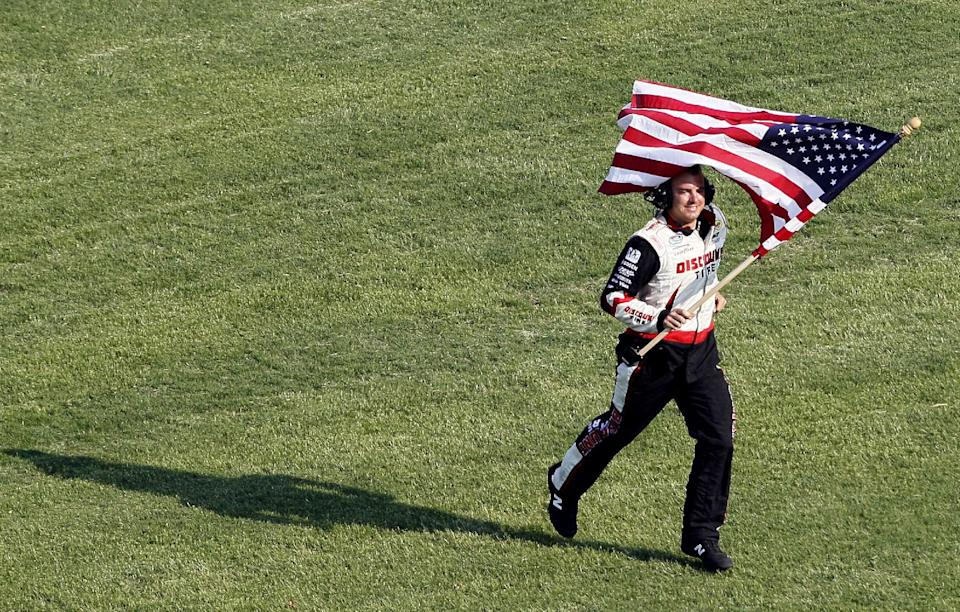 A crew member for race-winner Brad Keselowski runs with a United States flag for Keselowski following the NASCAR Nationwide Series History 300 auto race in Concord, N.C., Saturday, May 26, 2012. (AP Photo/Gerry Broome)