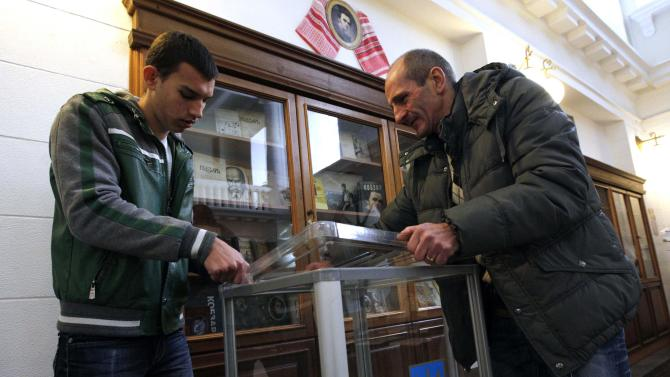 Election commission workers install a ballot box at a polling station in Kiev