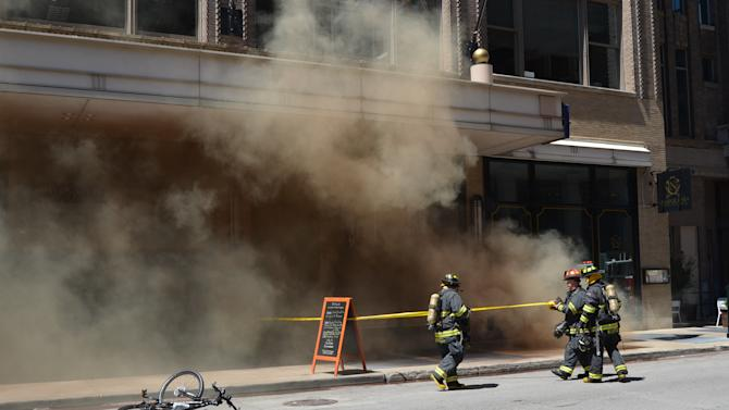 In a photo provided by the Indianapolis Fire Department, smoke rises through a grate on a sidewalk after a series of small transformer explosions Wednesday, Aug. 13, 2014, in downtown Indianapolis. The explosions about 1:30 p.m. outside the Circle Centre shopping and entertainment mall rattled windows and sent police officers rushing into the area to evacuate workers and other onlookers to a safe distance away, Indianapolis Fire Department Capt. Rita Reith said. (AP Photo/Indianapolis Fire Department, Capt. Rita Reith)