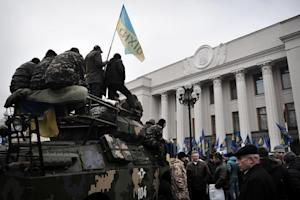 Maidan self-defence activists sit on an armoured vehicle …