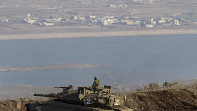 FILE - In this Tuesday, Nov. 13, 2012 file photo, an Israeli soldier on top a tank in position overlooking the Syrian village of Bariqa, close the Israel-Syria border, near Alonei Habashan in Golan Heights. Syrian rebels control almost all the villages near the frontier with the Israel-held Golan Heights, the Israeli defense minister said Wednesday, bringing the conflict dangerously close to the Jewish state and raising the possibility of an armed clash with the region's strongest power. (AP Photo/Ariel Schalit, File)