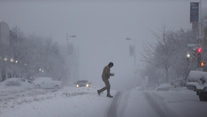 An unidentified man carries coffee to his vehicle across an unplowed street in Lawrence, Kan., Tuesday, Feb. 26, 2013.   The second major snowstorm in a week battered the nation's midsection Tuesday, dropping a half-foot or more of snow across Missouri and Kansas and cutting power to thousands.  Gusting winds blew drifts more than 2 feet high and created treacherous driving conditions for those who dared the morning commute. (AP Photo/Orlin Wagner)