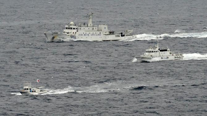 A  Japan Coast Guard vessel, right, and and a Chinese surveillance ship, top, follow a Japanese fishing boat near disputed islands called Senkaku in Japan and Diaoyu in China in the East China Sea Tuesday, April 23, 2013. A group of Japanese ultra-nationalists planned Tuesday to approach the islands on several fishing vessels and pleasure boats. The visit adds to risks of confrontation, however, with Chinese vessels circulating in the area. (AP Photo/Kyodo News) JAPAN OUT, MANDATORY CREDIT, NO LICENSING IN CHINA, HONG KONG, JAPAN, SOUTH KOREA AND FRANCE