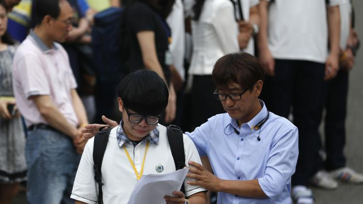 A representative of students who survived the April 16 ferry disaster cries while reading a letter as a teacher comforts him at Danwon Highschool in Ansan