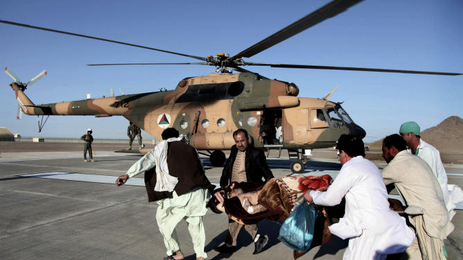 An injured Afghan man is evacuated to an Afghan Army helicopter in Farah, western Afghanistan, Thursday, April 4, 2013. Suicide bombers disguised as Afghan soldiers stormed a courthouse Wednesday in a failed bid to free more than a dozen Taliban prisoners in western Afghanistan, officials said. Tens of people, including the nine attackers were reported killed in the fighting. The assault in Farah province was the latest example of the Taliban's ability to strike official institutions despite tight security measures. (AP Photo/Hoshang Hashimi)