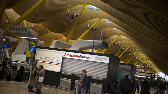 Passengers walk the closed American Airlines desk at Madrid Barajas T4 international airport in Madrid, Tuesday, Oct. 30, 2012. Spain's National Airport Authority said 19 flights between Madrid and Barcelona and the U.S. east coast were canceled Tuesday, adding to the 13 canceled on Monday, due to superstorm Sandy. (AP Photo/Daniel Ochoa de Olza)
