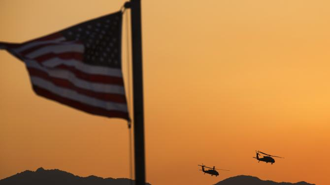 Two UH-60 Blackhawk helicopters carry U.S. Senator John McCain away after a Christmas Day visit to forward operating base Gamberi in the Laghman province of Afghanistan
