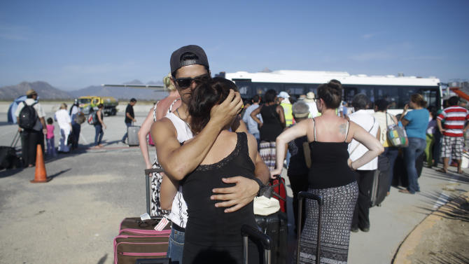 Jesus Guerrero, 24, of Mexico, hugs his girlfriend Ditte Smedegaard, of Denmark, as they wait in line to be evacuated out of Los Cabos, Mexico, Thursday, Sept. 18, 2014. Mexican authorities said 8,000 people, including tourists and locals anxious to leave, would be airlifted out on Thursday from Los Cabos following the blow from Hurricane Odile. (AP Photo/Victor R. Caivano)