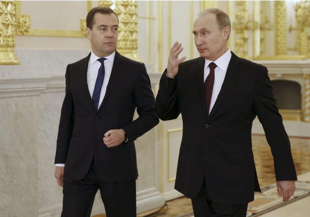 Russia's President Vladimir Putin talks to Prime Minister Dmitry Medvedev after delivering his annual state of the nation address at the Kremlin in Moscow