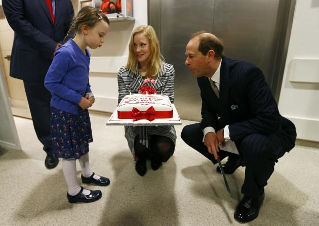 Britain's Prince Edward blows out the candles with Iris Filbee at the Royal Hospital in east London