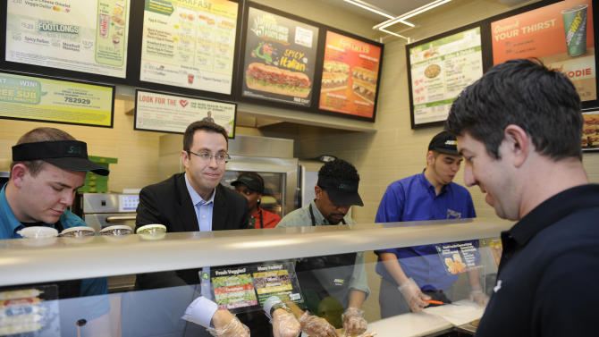 "IMAGE DISTRIBUTED FOR SUBWAY -  Jared ""The SUBWAY Guy"" Fogle, second from left, makes a sandwich for Ryan Kules, alumni director for Wounded Warrior Project, right, at a SUBWAY cafe at the Navy Exchange, Saturday, Nov. 10, 2012 in Bethesda, Md. SUBWAY restaurants donated $111,112.00 to Wounded Warrior Project. Kules is an Army veteran who served and was wounded in Iraq in 2005. (Photo by Nick Wass/Invision for SUBWAY/AP Images)"