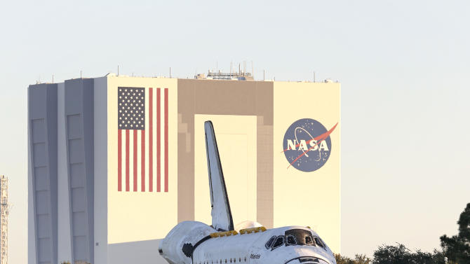 Space shuttle Atlantis make its way from the Vehicle Assembly Building to the Visitor Complex at the Kennedy Space Center, early Friday, Nov. 2, 2012, in Cape Canaveral, Fla. Atlantis began its slow journey to retirement Friday, riding atop 76-wheeled platform on the 10-mile trek to the Kennedy Space Center's main tourist stop. (AP Photo/Terry Renna)