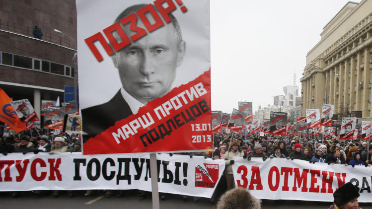 "People carry posters of Russian President Vladimir Putin with the words reading ""March Against the Scum and Shame"" during a protest rally in Moscow, Russia, Sunday, Jan. 13, 2013, with the banner reading ""Dissolution of the State Duma"". Thousands of people are gathering in central Moscow for a protest against Russia's new law banning Americans from adopting Russian children. (AP Photo/Misha Japaridze)"