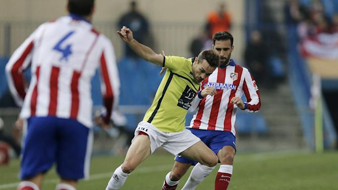 Atletico's Jesus Gamez duels for the ball with Hospitalet's A. Barrera during a King's Cup soccer match between Atletico de Madrid and Hospitalet, at the Vicente Calderon stadium in Madrid, Spain, Thursday, Dec. 18, 2014. (AP Photo/Daniel Ochoa de Olza)