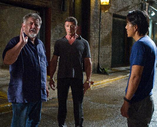 """This film image released by Warner Bros. Pictures shows director walter Hill, left, with Sylvester Stallone, and Sung Kang, right, on the set of """"Bullet to the Head."""" (AP Photo/Warner Bros. Pictures, Frank Masi)"""