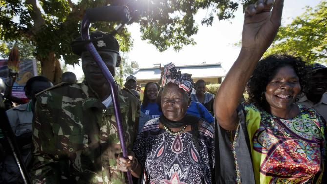 Sarah Obama, step-grandmother of President Barack Obama, waves her walking cane towards supporters in celebration before speaking to the media about her reaction to Obama's re-election in the U.S. presidential election in the garden of her house in the village of Kogelo, western Kenya, Wednesday, Nov. 7, 2012. (AP Photo/Ben Curtis)