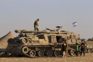 An Israeli soldier stands on top of a military vehicle in a base near Sa'ad in the southern district of Israel