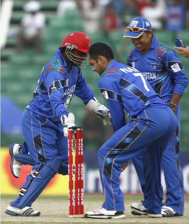 Afghanistan's wicketkeeper Shahzad breaks the wicket with Zadran to dismiss Pakistan's captain Misbah-ul-Haq successfully during their Asia Cup 2014 ODI cricket match in Fatulla