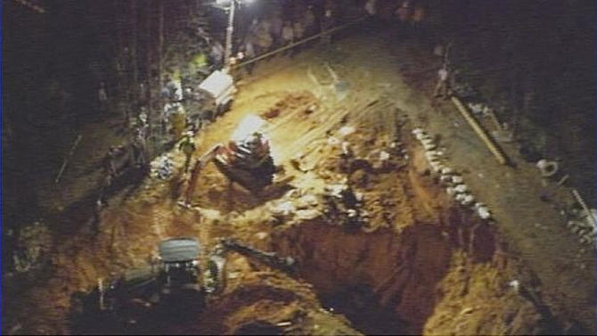 In this image made from video and provided by WSOC-TV Charlotte, authorities work to rescue two children at a construction site, Sunday, April 7, 2013, in Stanley, N.C. Two television stations are reporting that two children are trapped under a home under construction in Lincoln County near Charlotte. WBTV and WSOC report firefighters from several places, including Charlotte, are on the scene Sunday night. (AP Photo/WSOC TV)